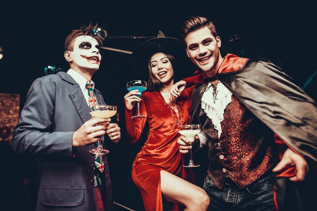 Young Happy People in Costumes at Halloween Party