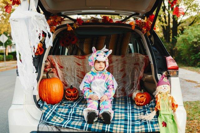 Trick or trunk. Sad upset baby in unicorn costume celebrating Ha